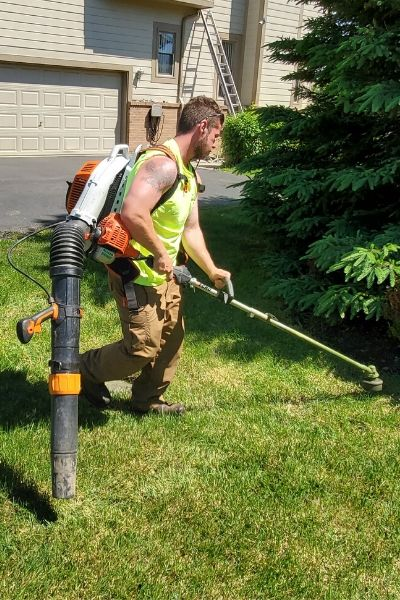 A member of the Priority One Lawn Care Team using a edger during a lawn servicxe.