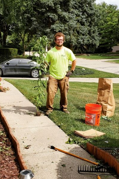 A member of the Priority One Lawn Care team gathering clippings for disposal.