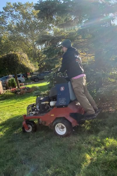 A member of the Priority One Lawn Care team using a stand on aerator to preform a lawn aeration service.